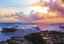 Colorful view of waves washing over rocks around sunset.